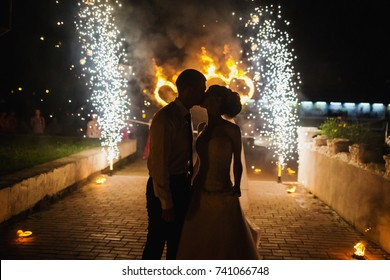 The bride and groom kiss on the background of a wedding spree. Sensual photo