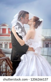 Bride and groom kiss under the veil in the old town on the background of a cloud on an autumn day close-up.