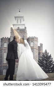 A bride and groom kiss while holding hands with the Logan LDS Temple in the background and a sunbeam shining on their faces.