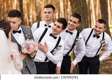 Bride and groom kisses near friends, groomsmen with bow ties and suspender looks at newlyweds at wedding day