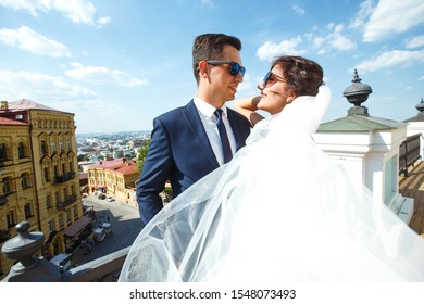 Bride and groom kisses tenderly in the shadow of a flying veil. A stylish bridegroom in a black suit gently embraces a beautiful bride in a white dress with a flying veil. Together. Wedding. Love.