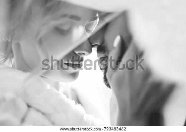 新郎新婦は、空を舞うベールの影に優しくキスし、美しい写真を撮ります。みんな楽しんで。セクシーなキススタイリッシュな恋人同士の接写。白黒
