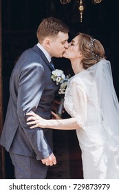 bride and groom kissing at church door after wedding matrimony. traditional religious wedding ceremony