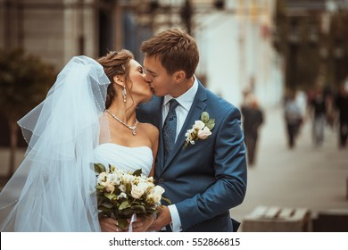bride and groom kissing on a background of the city.