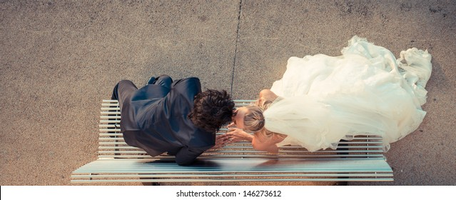bride and groom kissing on an iron bench taken from up above
