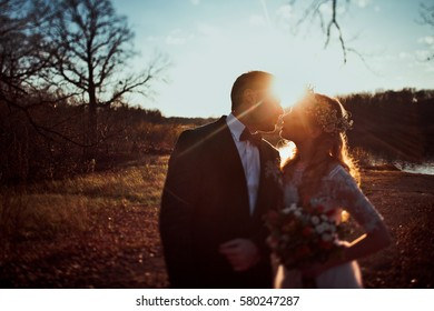 bride and groom kissing on sunset on rustic autumn wedding