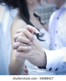 A bride and groom kissing on their wedding day, focus on hands