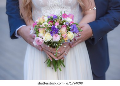 Bride and groom kissing on the wedding day. Closeup on the elegant bridal bouquet.