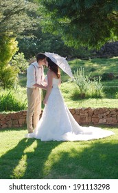 Bride and groom kissing with parasol in outside garden wedding ceremony