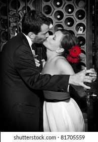 A bride and groom kissing in the wine cellar after their wedding. Black and white with a color treatment to bring out the red flowers in the bride's hair.