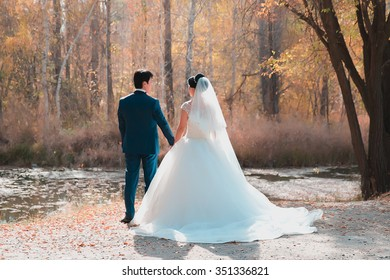 Bride and groom look at each other in autumn.