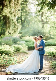 Bride and groom look gorgeous walking in a green summer park