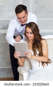 Bride and groom looking photos on the tablet