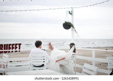Bride and groom are looking towards the sea