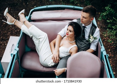 bride and groom in love in a retro car