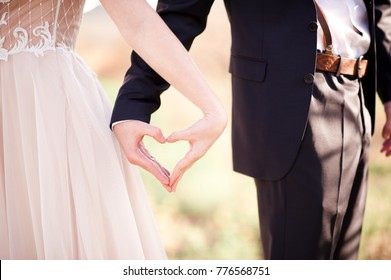 Bride and groom making heart by hands outdoors close up. Wedding day.