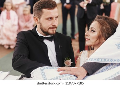 Bride and groom making oaths  and priest holding their hands on holy Bible. Wedding matrimony in church. Exchanging vows. Emotional romantic moments