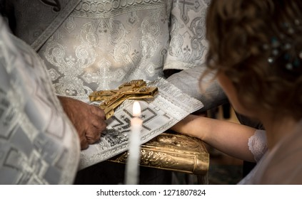 Bride and groom, making oaths putting their hands on the Bible. The priest holds the cross.  Wedding matrimony in church. Exchanging vows.