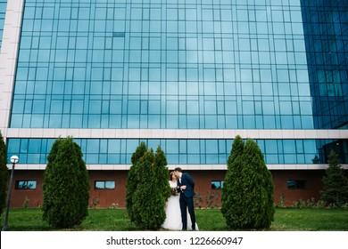 Bride and groom near the green bush