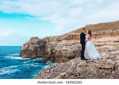 Bride and groom near the ocean hugging each other