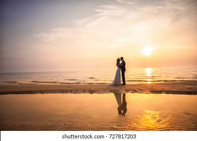 Bride and groom, newlyweds, honeymoon on the beach sunset sun