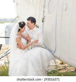 Bride and groom next to old aircraft. Wedding summer couple together posing against brick wall.