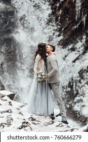bride and groom on the background of a mountain waterfall