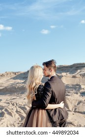 the bride and groom on the background of sand