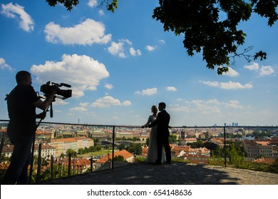 the bride and groom on the background on view of old  town Prague. Czech Republic. videographer make video. happy married heterosexual couple