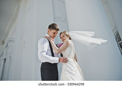 The bride and groom on the background of the white Church.