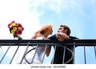 A bride and groom on a balcony