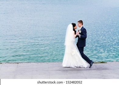 the bride and groom on the banks of the river