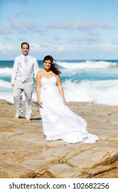 bride and groom on beach rocks