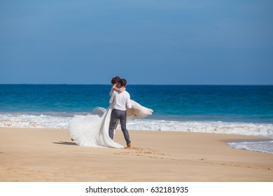 Bride and groom on the beach with a romantic moment, dancing on sea cost