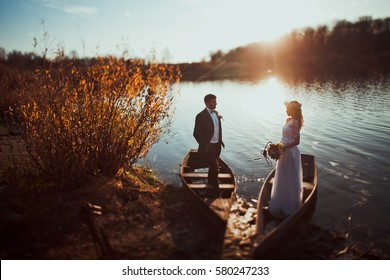 bride and groom on in boats on sunset on rustic autumn wedding