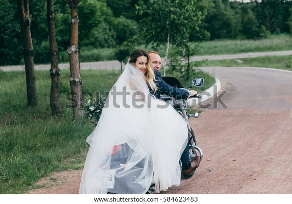 Bride and groom on the cool red bike