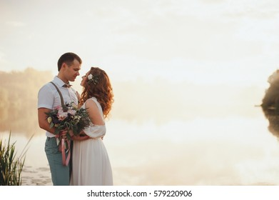the bride and groom on a lake the background of beautiful sunset