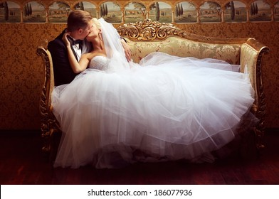 Bride and groom on a luxury hotel, kissing on a sofa