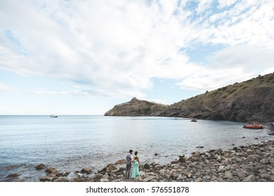 The bride and groom on nature in the mountains near the water. Suit and dress color Tiffany. Stand on the beach holding hands.