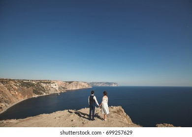 bride and groom on the precipice of the mountain. the ocean. sea.