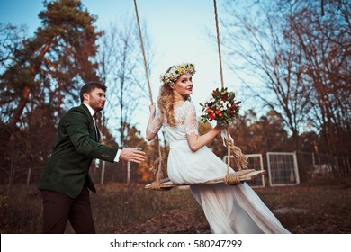 bride and groom on swing on rustic autumn wedding