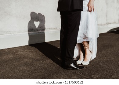 Bride and groom on their wedding forming a heart with the shadow of their faces on a wall. In front, you see the feet of the bride. She is lifting her dress