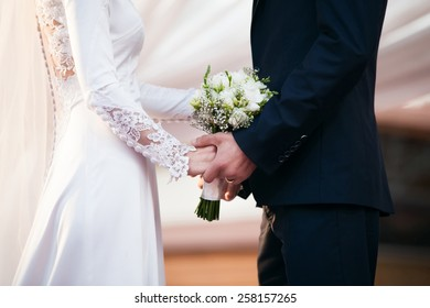 Bride and groom on wedding day. Groom hold on bride's hands. Focused on wedding bouquet