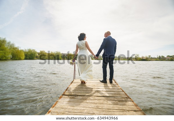 The bride and groom on the wooden bridge going to the distance