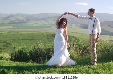 Bride and groom outside garden wedding with African Natal Midlands mountain scenery background