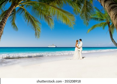 bride and groom with palm trees on a tropical beach