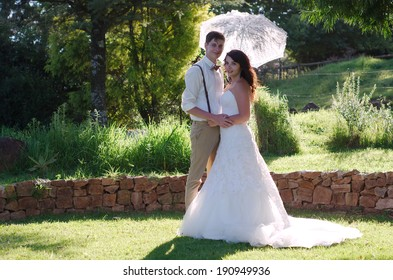 Bride and groom with parasol outside garden wedding ceremony