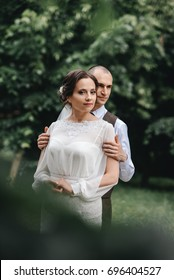 Bride and groom in a park kissing.couple newlyweds bride and groom at a wedding in nature green forest are kissing photo portrait.Wedding Couple