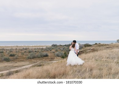 Bride and groom at a photo session close to the sea, on a cliff