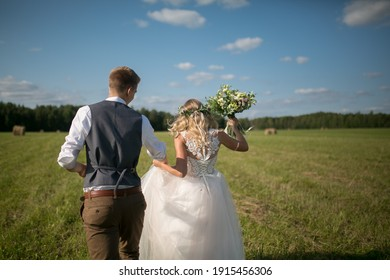The bride and groom photographed from behind in a field